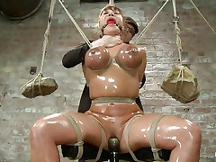 This is a nice sight! Busty milf Ava is oiled up and tied hard. Her big boobs are squeezed with rope and at the end of the rope two big and heavy rocks are used as weights to keep it tight. Then her mistress comes and fills her shaved pussy with a dildo while using a vibrator on her clit. It's hot!